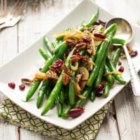 This easy side dish is perfect for Thanksgiving. Crisp green beans get tossed with caramelized onions, toasted pecans, and dried cranberries.   www.themessybakerblog.com