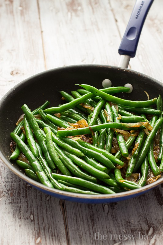This easy side dish is perfect for Thanksgiving. Crisp green beans get tossed with caramelized onions, toasted pecans, and dried cranberries. | www.themessybakerblog.com