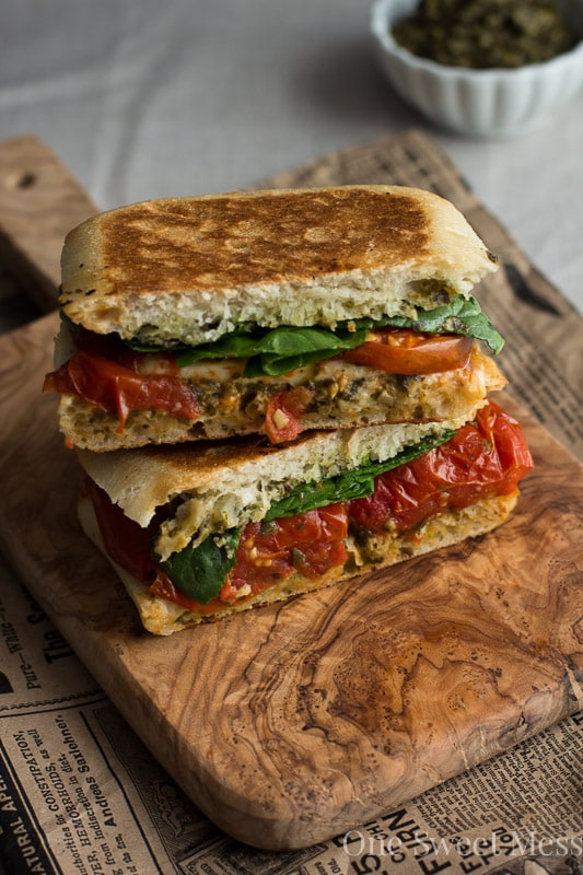 is piled high with thick slices of mozzarella, sweet roasted tomatoes ...