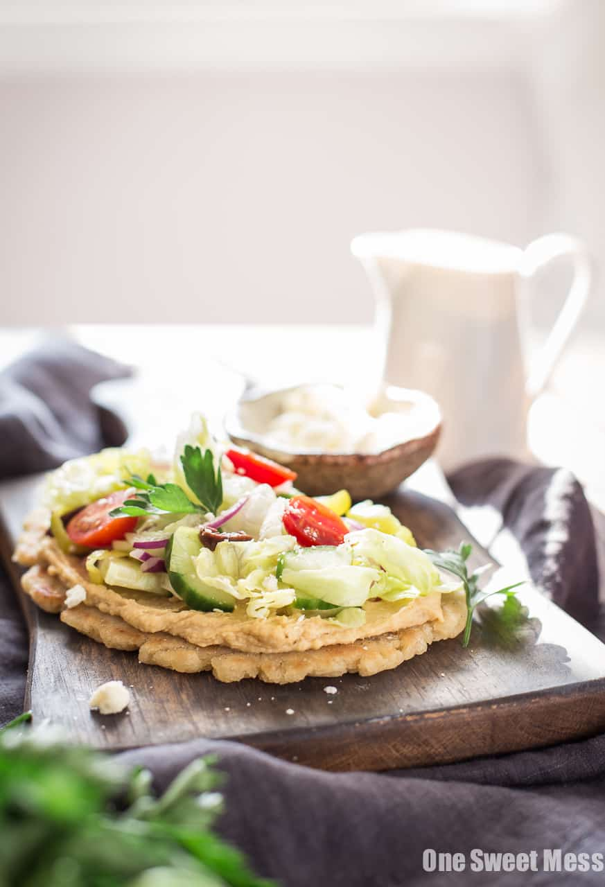 Gluten-Free Greek Salad Naan Pizza: Gluten-Free Naan smeared with creamy hummus and topped with a mound of fresh Greek salad.